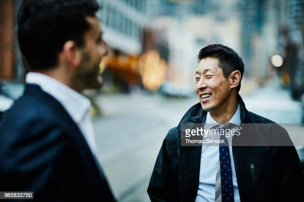 smiling business colleagues in discussion while standing on city street - korean ethnicity stock pictures, royalty-free photos & images