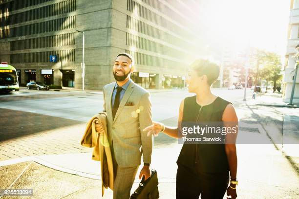 Smiling business colleagues in discussion while walking on city sidewalk during morning commute