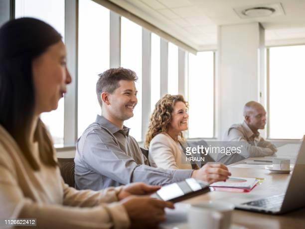 smiling business colleagues in meeting at office - shareholder's meeting stock photos and pictures