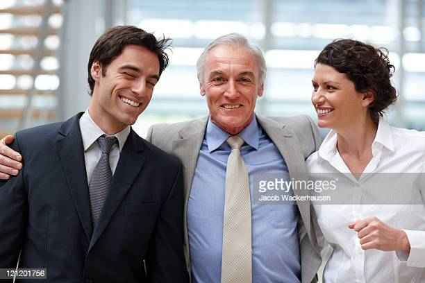 Collègues de travail souriant debout ensemble dans le bureau