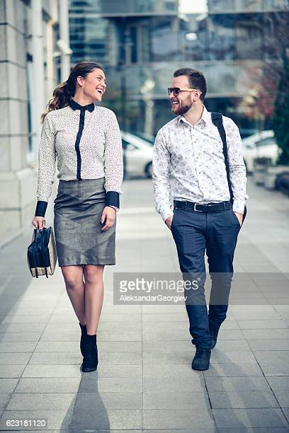 Smiling Business Colleagues Walking on the Street and Talking