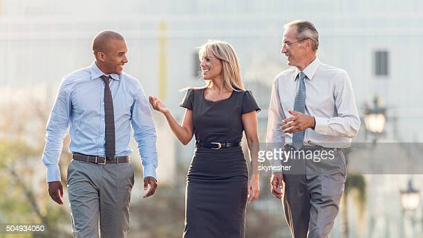 Smiling business colleagues walking outdoors and discussing.