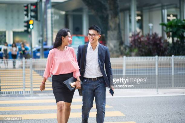 smiling business couple crossing the street - businesswear stock pictures, royalty-free photos & images