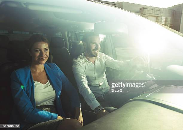 Smiling business couple going on a business travel by car.