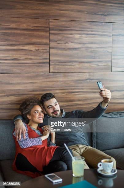 Smiling business couple taking selfie while sitting on sofa in cafe