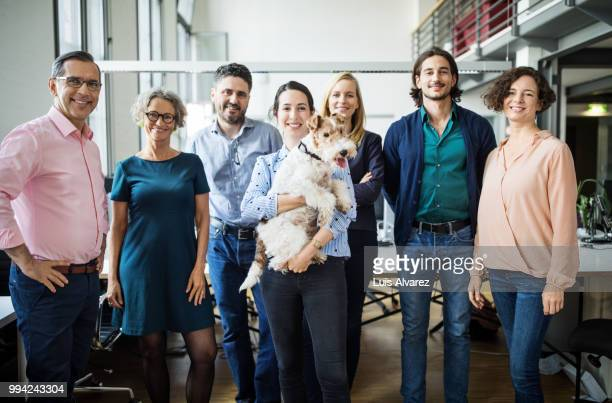 Smiling business entrepreneurs standing with dog