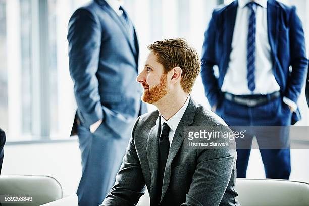 Smiling business executive sitting in office lobby