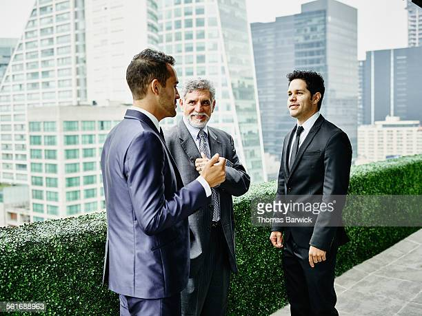 Smiling business executives in discussion on deck