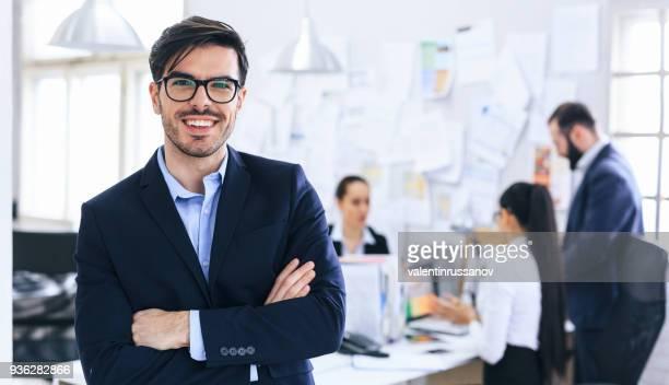 empresario sonriente con los brazos cruzados - gobierno fotografías e imágenes de stock