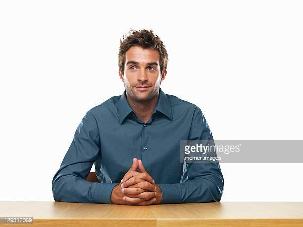 Smiling business man sitting at table with hands clasped