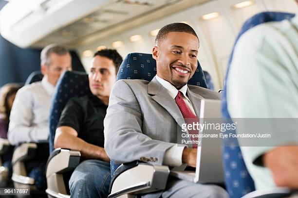 smiling business man using computer on airplane