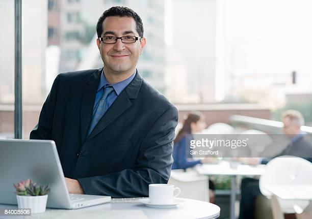 ビジネス男笑顔、コンピュータのカフェです。