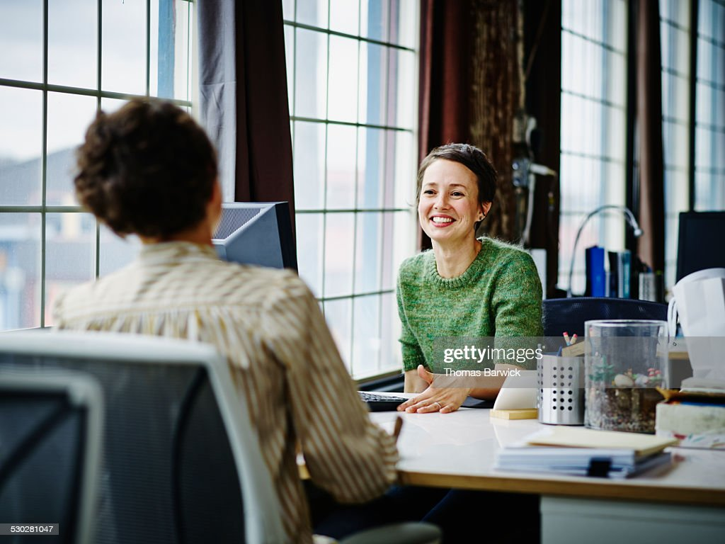 Smiling business owners at workstation in office : Stock Photo