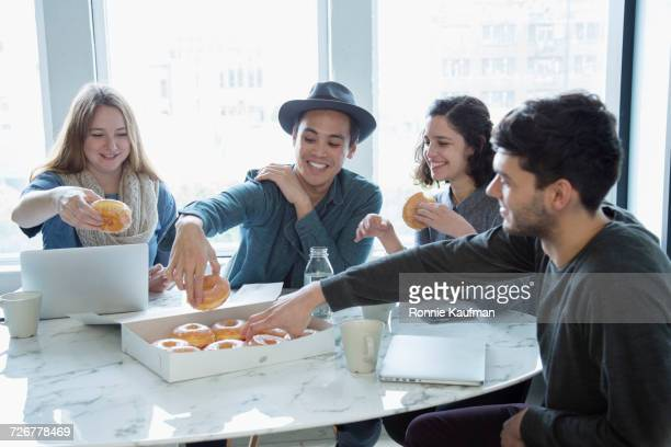 Smiling business people eating donuts in conference room