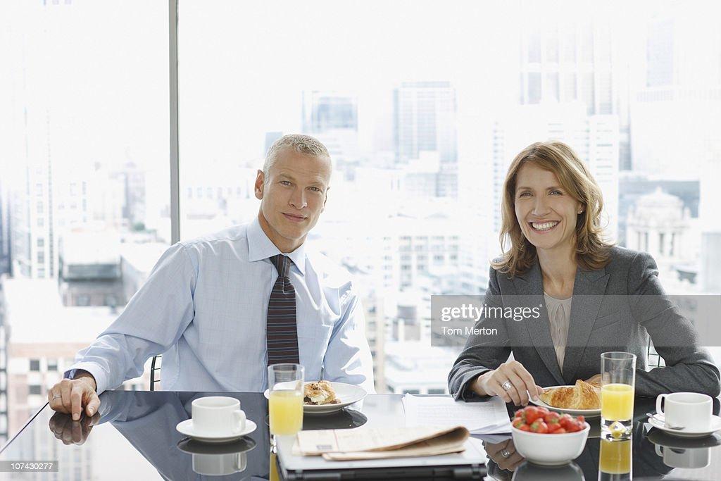 Smiling business people having breakfast : Stock Photo