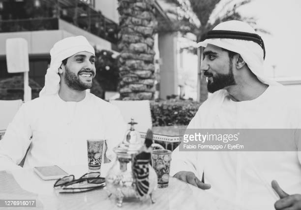 smiling business people having discussion while sitting at cafe - abu dhabi stock pictures, royalty-free photos & images