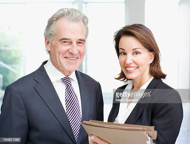 smiling business people holding files in office - full suit stock pictures, royalty-free photos & images