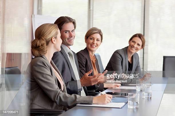 Souriant hommes d'affaires réunis autour d'une table dans la salle de conférence