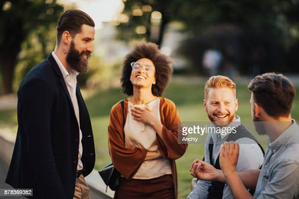 smiling business people outdoors in the street on coffee brake - capital cities stock pictures, royalty-free photos & images