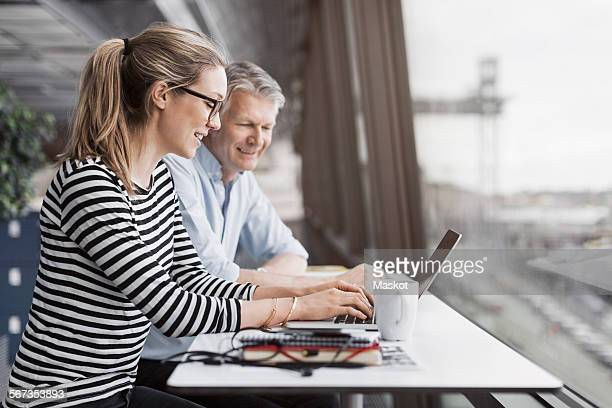 Smiling business people sitting at counter by window in office