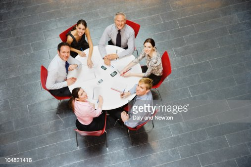 Smiling Business People Sitting At Round Table And Having