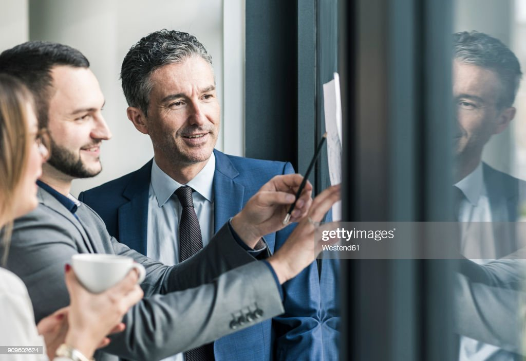 Smiling business people talking in office at the window : Stock-Foto
