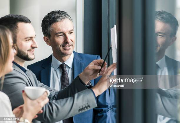 smiling business people talking in office at the window - geschäftsleben stock-fotos und bilder