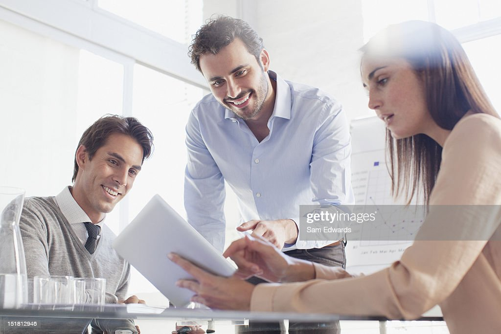 Smiling business people using digital tablet in meeting : Stock Photo