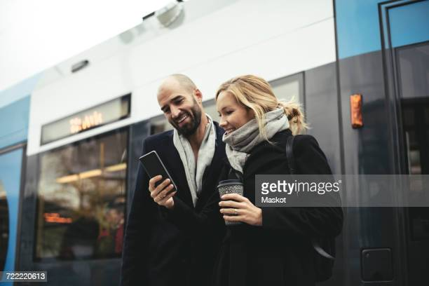 smiling business people using mobile phone while standing against tram - tram stockfoto's en -beelden