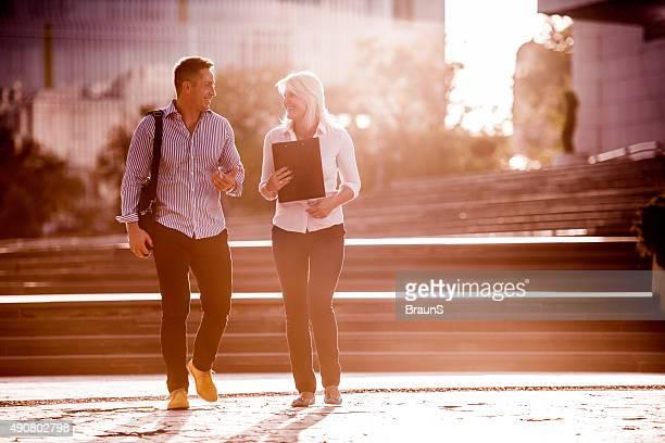 Lächelnde Geschäftsleute gehen auf der Straße und Kommunikation.