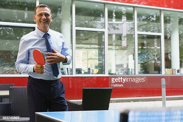 Smiling business person playing table tennis at creative office