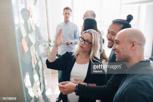 Smiling business team looking at adhesive notes in board room during meeting
