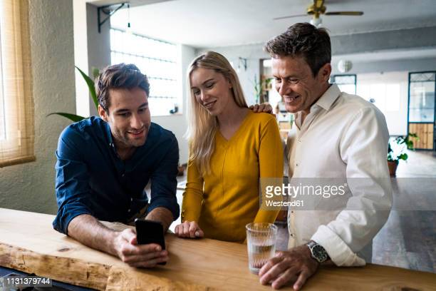 smiling business team looking at cell phone together in loft office - team photo ストックフォトと画像