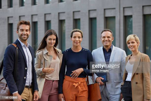 smiling business team standing against building - smart casual stock pictures, royalty-free photos & images