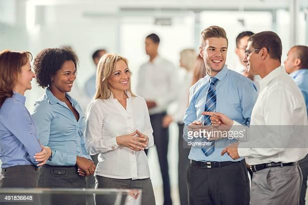 Sonriendo negocios equipo de pie juntos y la comunicación.