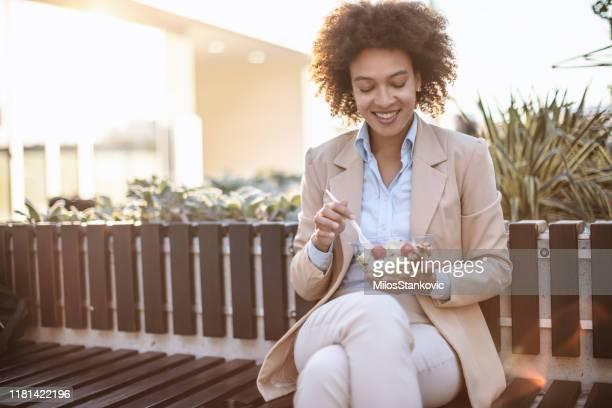mujer de negocios sonriente comiendo una ensalada de verduras al aire libre - lunch fotografías e imágenes de stock