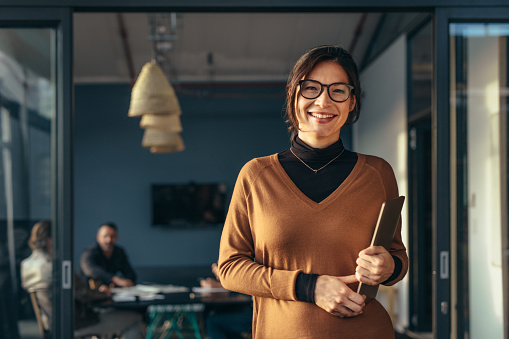 Smiling business woman in casuals at office 1030429684