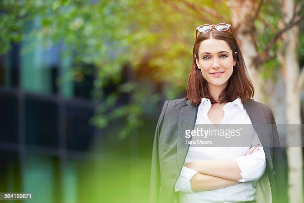 Smiling business woman in park outside offices