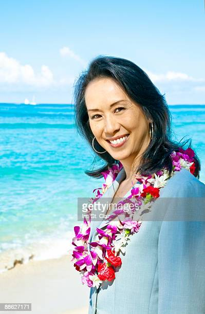 smiling business woman on beach with leis - lei day hawaii stock pictures, royalty-free photos & images