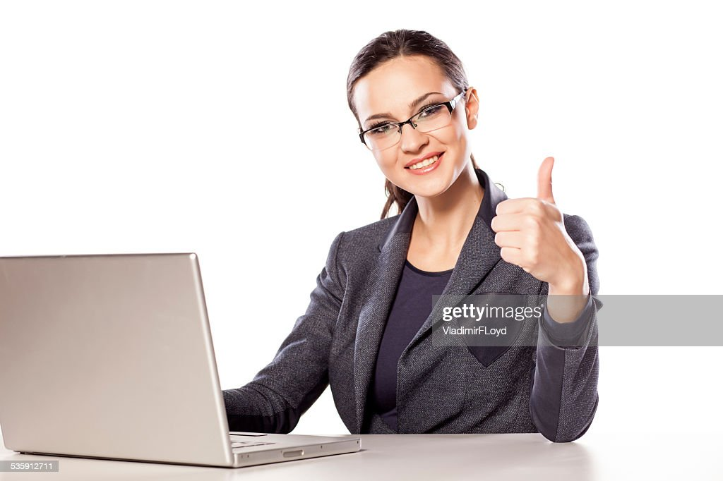 Smiling business woman showing thumb up next to her laptop : Stock Photo