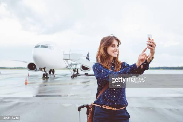 Lächelnde Geschäftsfrau Selfie vor Flugzeug im Gespräch