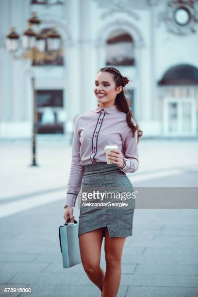 Smiling Business Woman Walking on City Street with Coffee