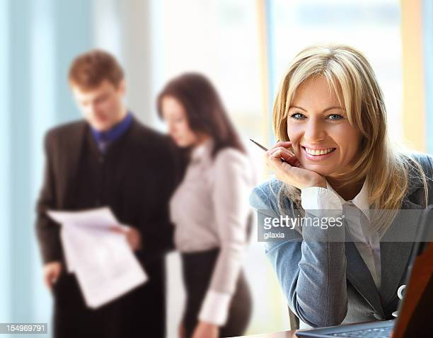 Smiling business woman with associates in background.