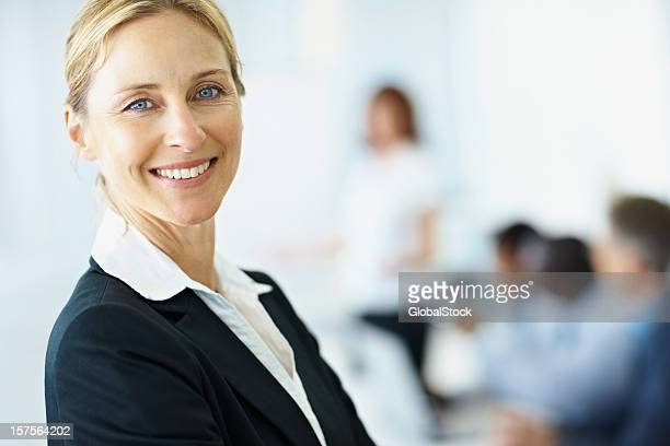 Smiling Business woman with colleagues in background