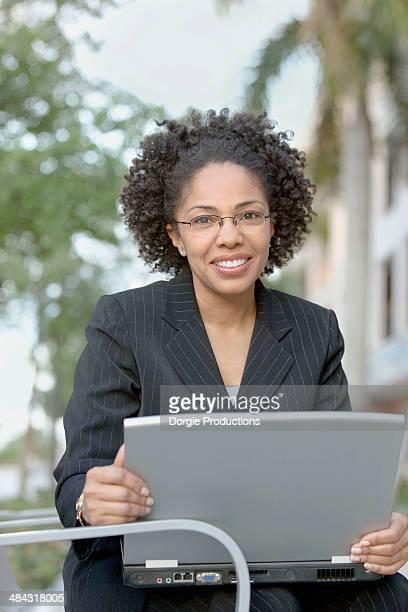 Smiling business woman with laptop portrait