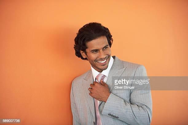 smiling businessman adjusting his tie - oliver eltinger stock-fotos und bilder