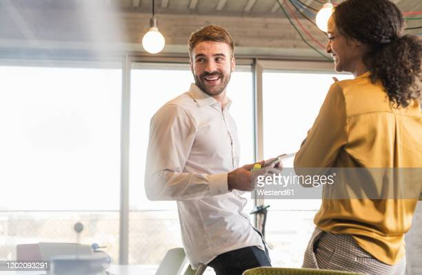 smiling businessman and businesswoman having a meeting in office - founder stock pictures, royalty-free photos & images