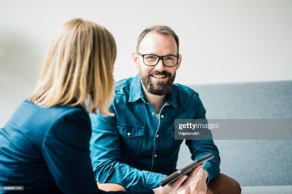 Smiling businessman and businesswoman in office lounge : Stock-Foto