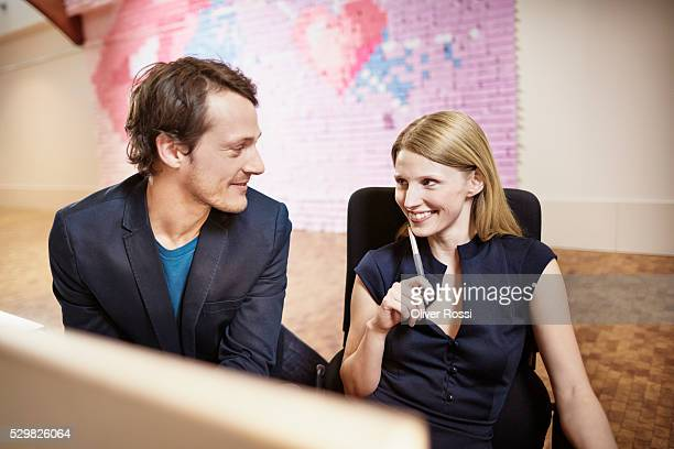 smiling businessman and businesswoman in office - work romance stock pictures, royalty-free photos & images