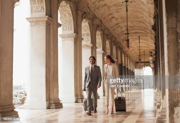 Souriant Homme d'affaires et Femme d'affaires en levant vos valises le long couloir de Venise